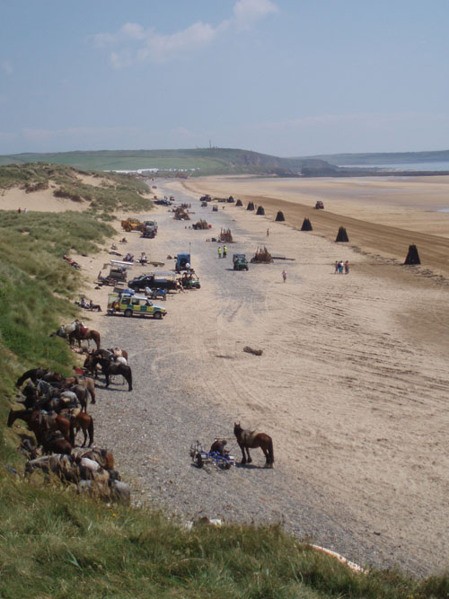 """View towards the south. You can see a tractor """"combing"""" the sand next to the wood stacks"""